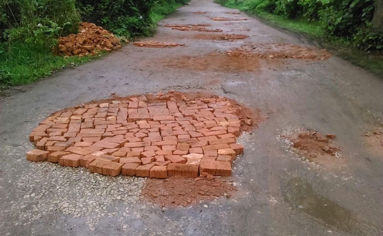 В Липках ямы на дорогах заделали кирпичами и землей