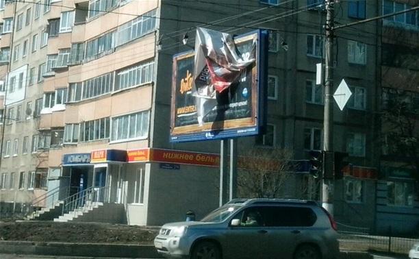 На ул. Октябрьской над дорогой развевается оторвавшийся кусок рекламной вывески