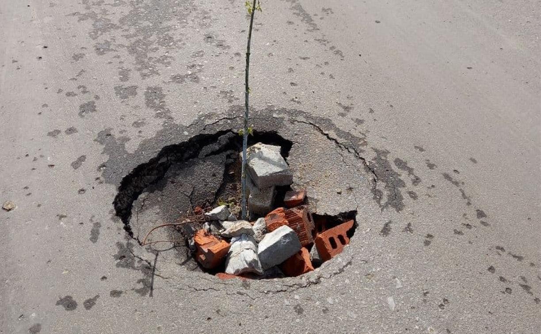 Яму на дороге в Мясново «залатали» кирпичами и веточкой