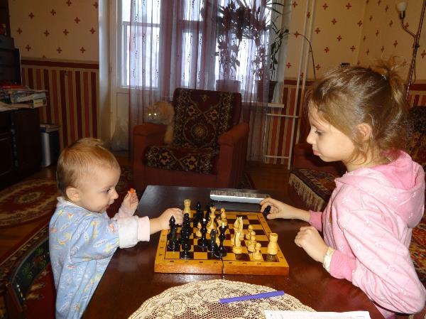 старшая учит младшую играть в шахматы