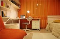 Детская комната поделена на две зоны с помощью цвета: у младшего сына оранжевое настроение распространяется на большей площади, у старшего это один, но крупный акцент – яркий диван., Фото: 7