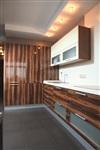 Мебель на кухне выстроена по двум стенам. Фасады – под дерево, что перекликается с деревянными элементами в гостиной, Фото: 1