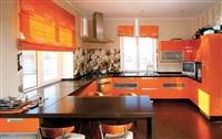 Для оформления кухни хозяйка предпочла оранжевый цвет – «живой, аппетитный». Столешницы выполнены из искусственного камня. На полу – керамогранит, уложенный бесшовно. Ближе к барной стойке и входу в гостиную его сменяет паркетная доска того же темного оттенка. По потолку эта смена зон «проложена» зеркальной полосой. , Фото: 2
