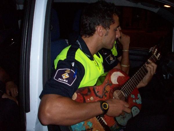 Полицейский Пальмы-де-Мальорка играет на гитаре, одолженной у уличных музыкантов.))